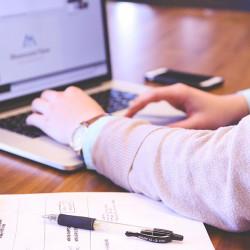 Skrivebord med notatark, kulepenn, en kopp te og en person som skriver på datamaskin. Mobiltelefon ligger i bakgrunnen. Man kan ikke se ansiktet til personen.