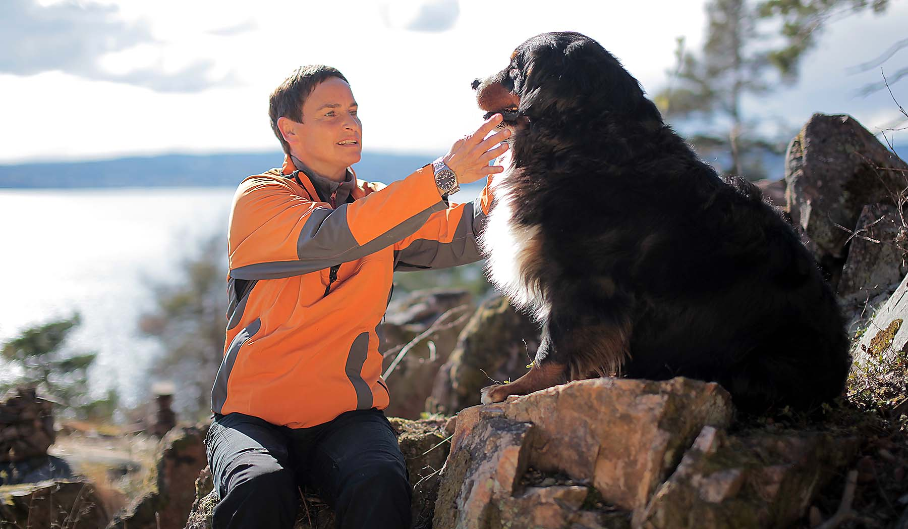 Dame til venstre klør en hund under haken. I skogen med utsikt over fjorden. Berith. Cath Gulbrandsen. er hundemassør.
