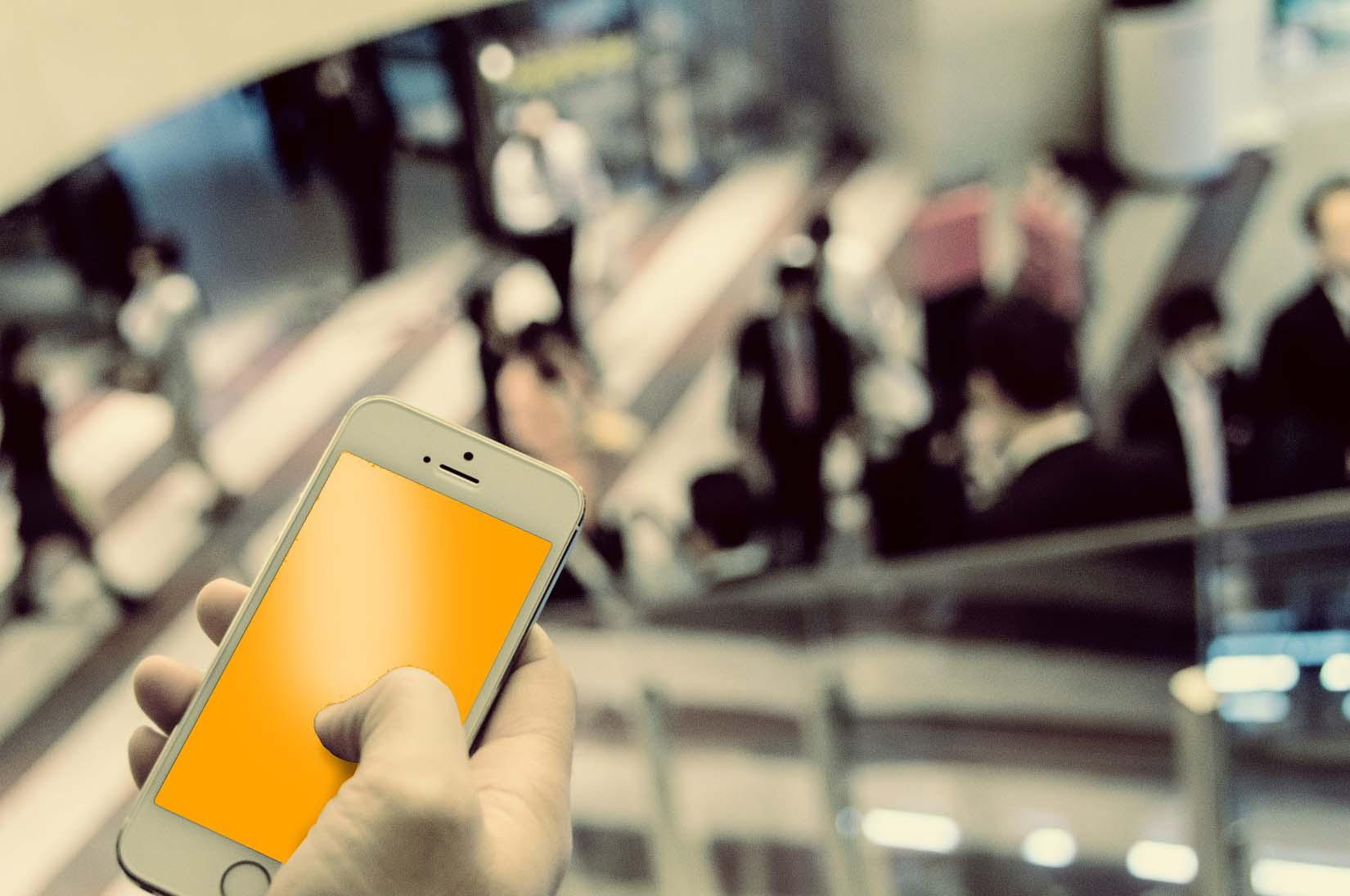 En hånd holder en mobiltelefon. Bakgrunnen er uklar, men kan minne om inngangspartiet til en stor kontorbygning eller en flyplass.