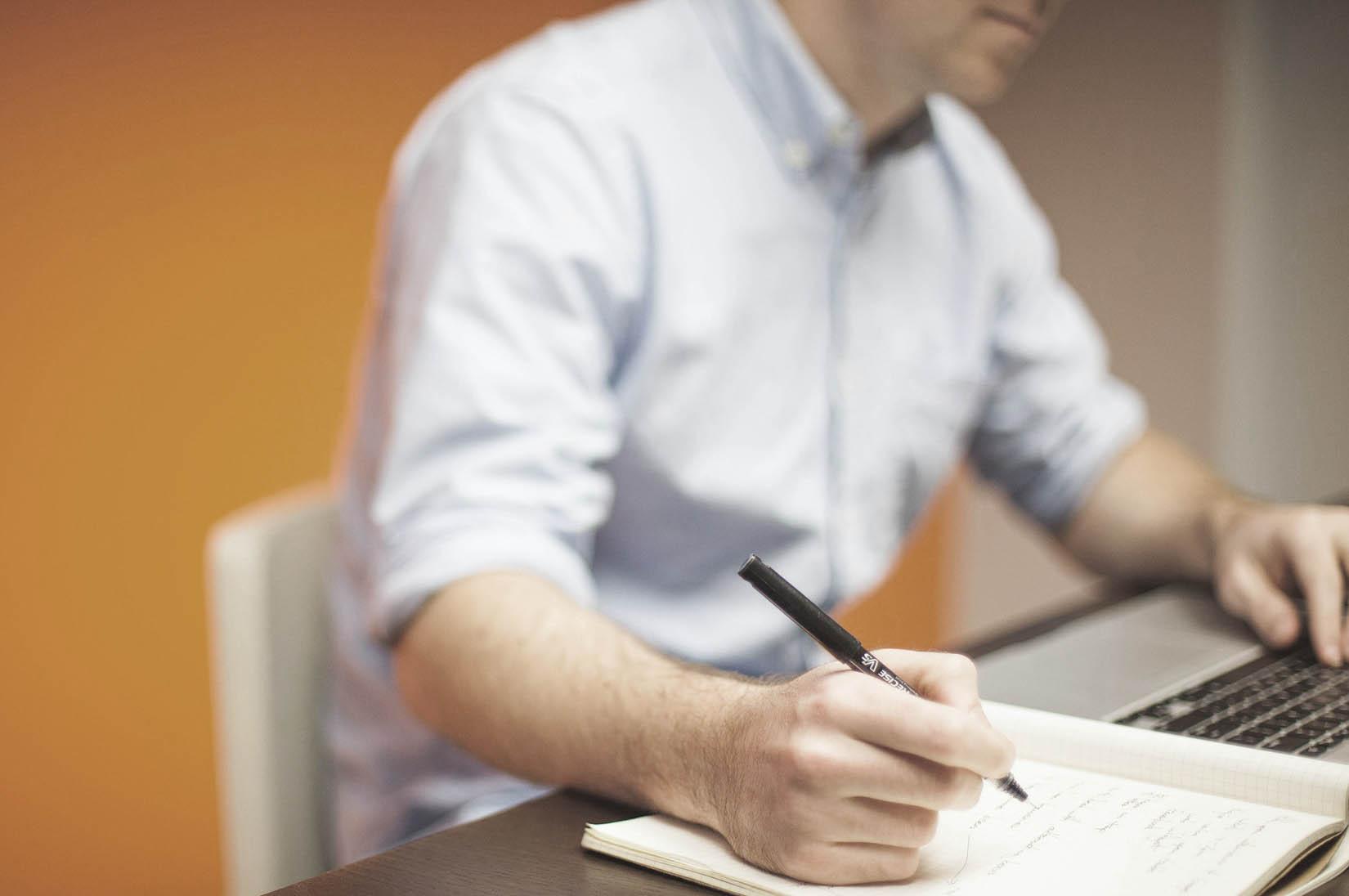 Mann skriver på et ark. Ved siden av er en PC.