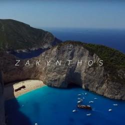 En sandstrand inne i en vk omgitt av høye klipper. Blå sjø. Turistbåter. Pent vær. Bildet er tatt på den greske øya Zakynthos.