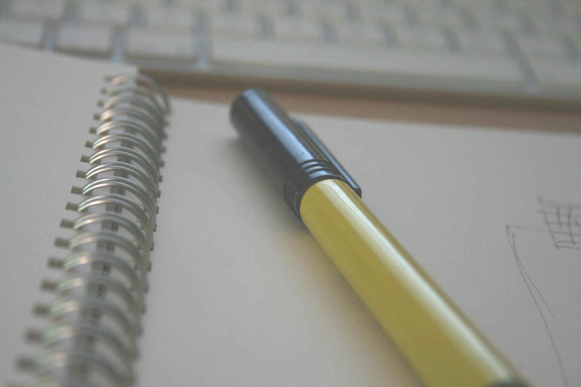 Nærbilde av en tusj som ligger oppå en notatblokk. I bakgrunnen skimtes tastaturet til en datamaskin. Bildet er litt grått og tåkete.
