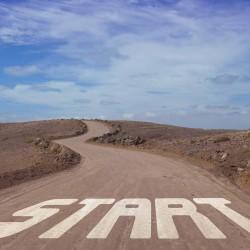 """En grusvei strekker seg gjennom en gråbrun ørken. I starten av veien står det """"Start"""". Veien ender i horisonten."""