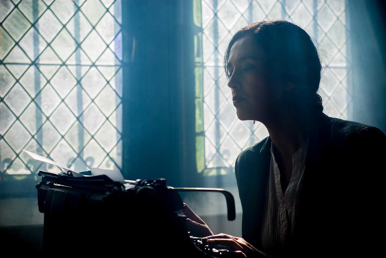Kvinne skriver på gammeldags skrivemaskin i motlys.