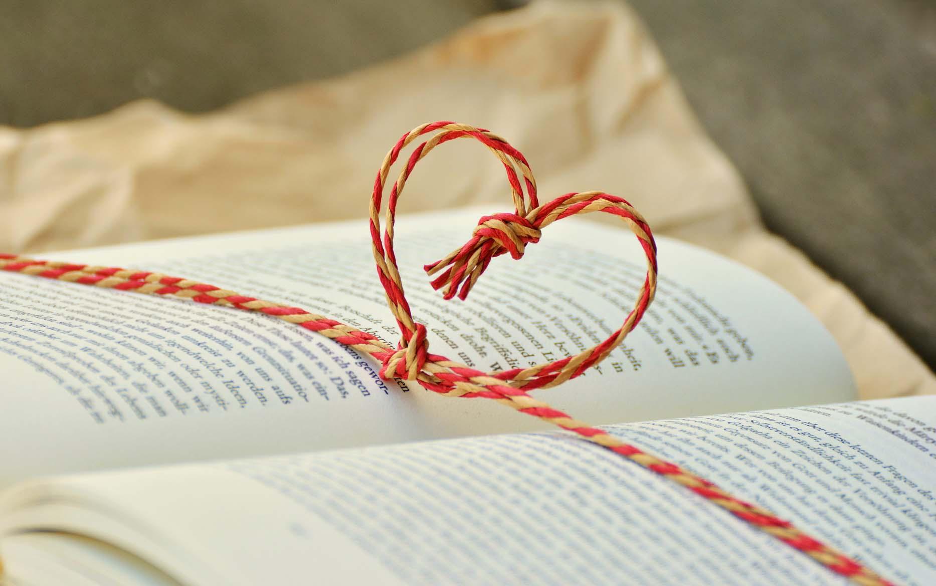 Oppslått bok med en rød snor rundt som med en knute danner et hjerte. I bakgrunnen innpakningspapir, boken er tdyeligvis akkurat åpnet som en pakke.