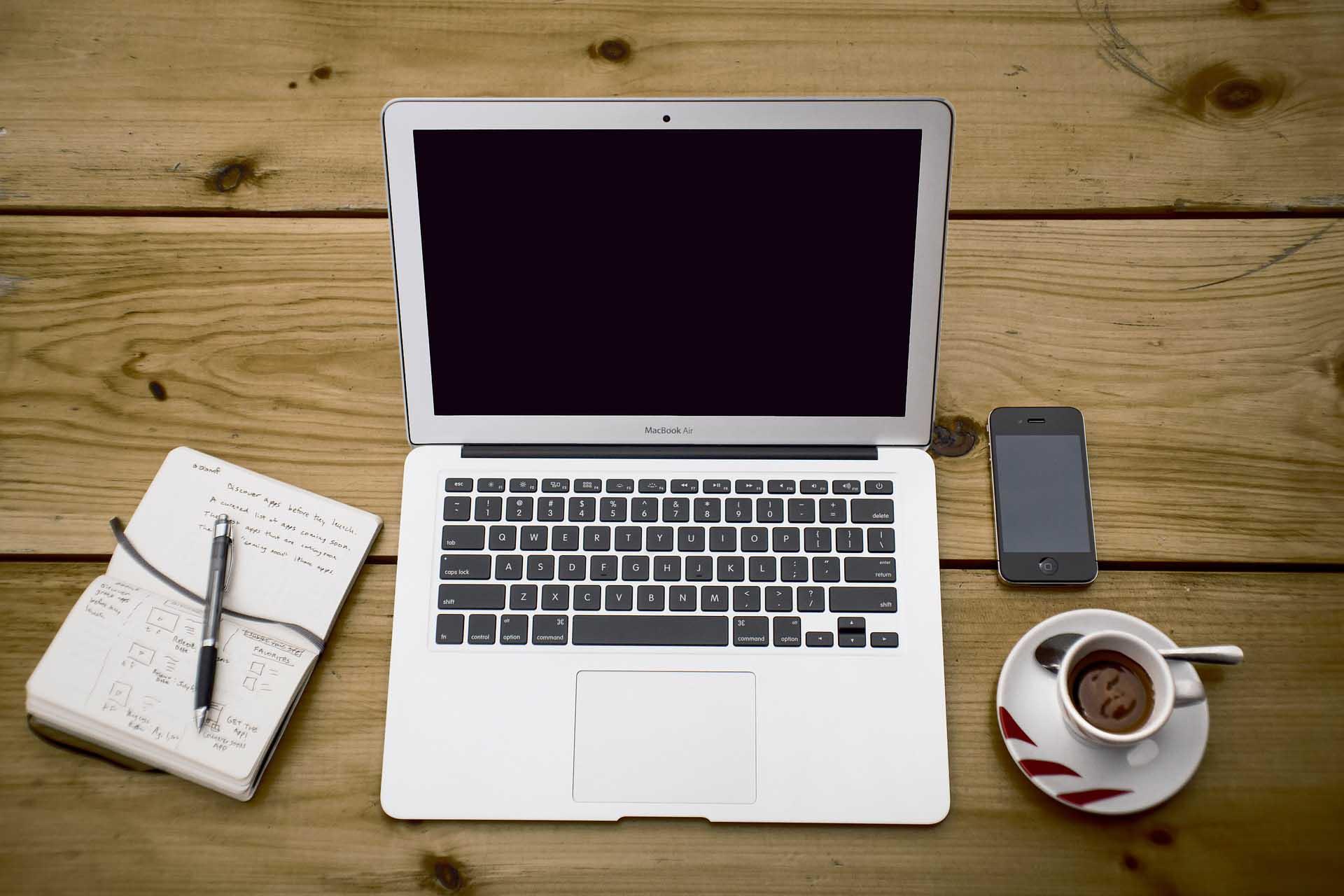 Bærbar datamaskin står på et bord som ser litt hytteaktig ut, ved siden av er notatblokk, kaffekopp og mobiltelefon. Skjermen er mørk.