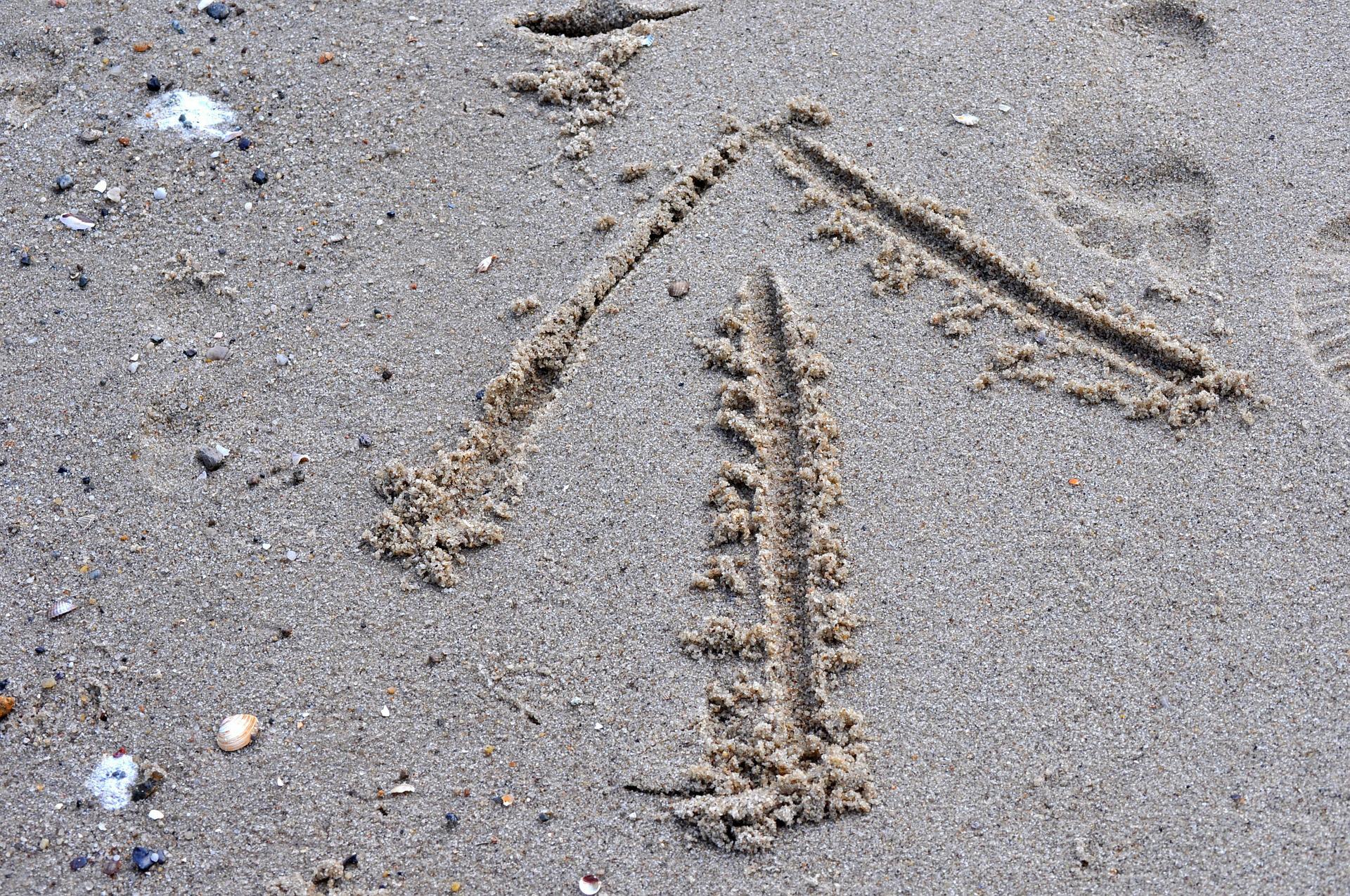 En pil er tegnet i sanden, antagelig ved stranden.