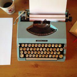 Gammeldags skrivemaskin, lys grønn, på et bord. Ved siden av står en kaffekopp. Det ligger også et papir og en bok på bordet.