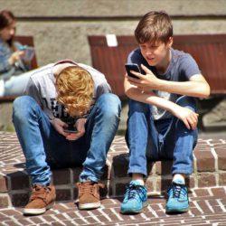 To gutter sitter i en skolegård og leser på sine mobiltelefoner.