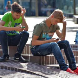 To gutter leser på sine mobiltelefoner, de sitter i en trapp ute.