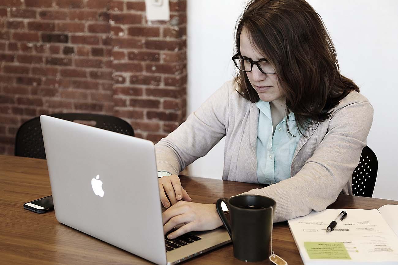 Ung kvinne sitter med PC. Kopp te. Hendene på tastaturet. Briller. En smule misfornøyd.