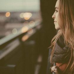 Ung kvinne på balkong, ser på utsikten på kvelden, bymiljø.