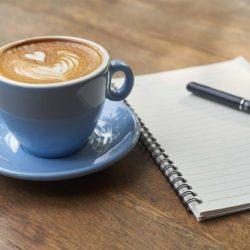 Kaffekopp med melk formet som et hjerte. Ved siden av en notisbok.