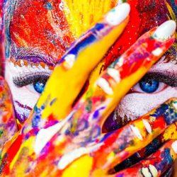 Ansikt med påmalt maling i mange farger. Hånd dekker ansiktet. Blå øyne ser rett i kamera.