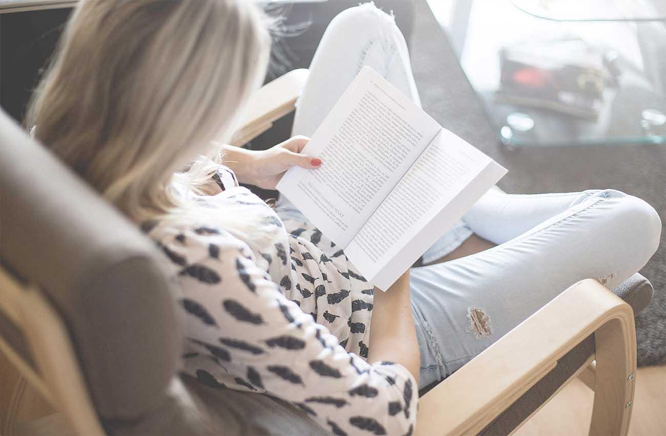 Kvinne sitter i stol hjemme og leser en bok.
