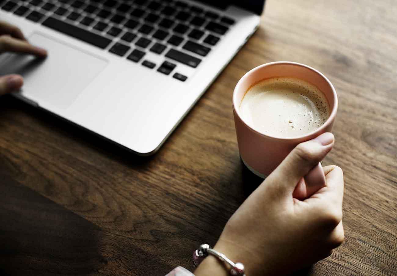 Tastatur. Hånd. Kaffekopp.